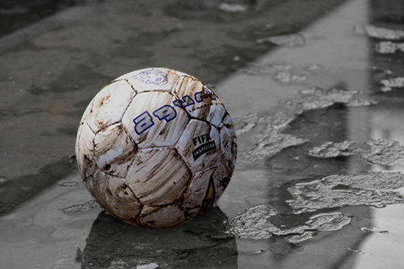 and old football laying in a puddle